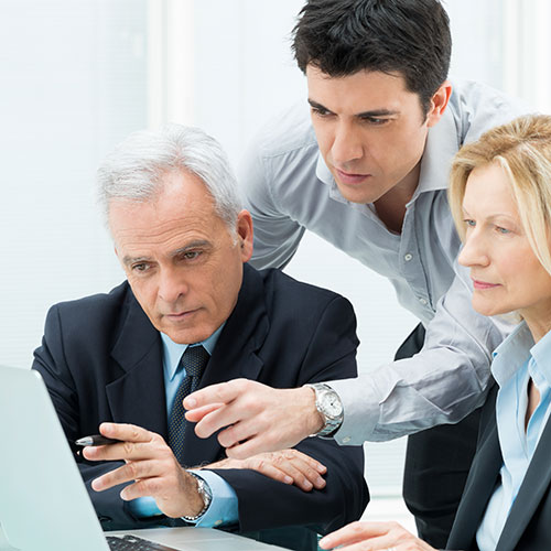 Kaksi miesät ja nainen tekevät yhdessä töitä tietokoneella